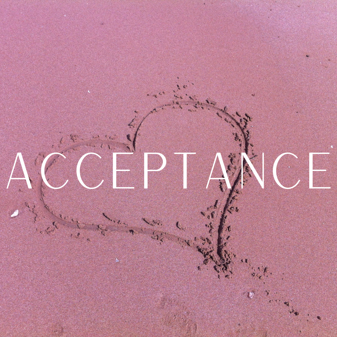 The word Acceptance written over a heart drawn in pink sand.