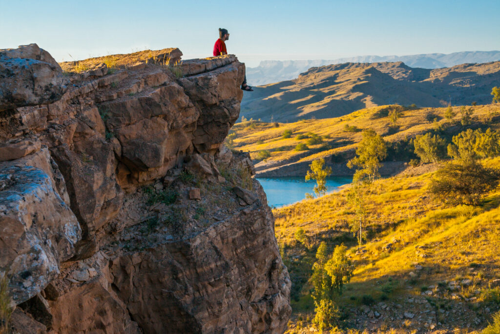 Person sitting on the cliff of a mountain overlooking the valley.