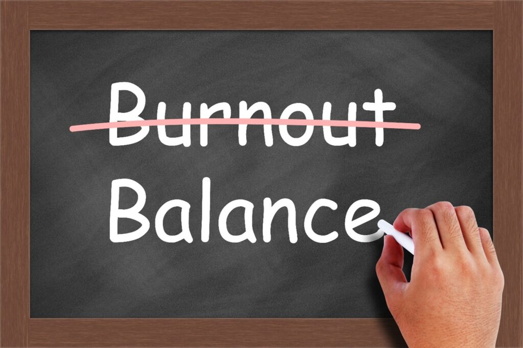 """Image of a chalkboard with the word """"burnout"""" crossed out and replaced with """"balance""""."""