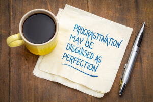 Coffe mug and a napkin that says procrastination may be disguised as perfection