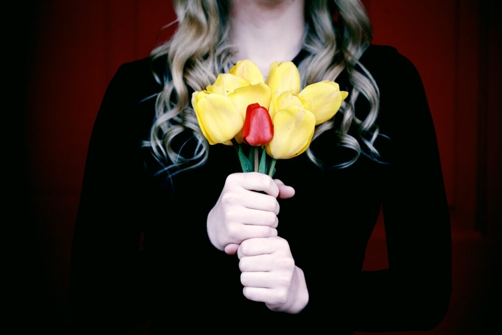 Woman holding yellow and red tulips